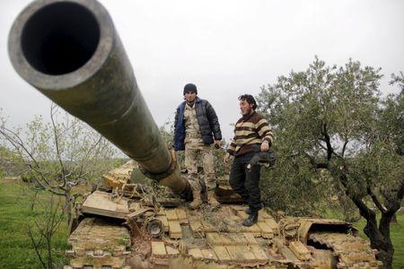Rebel fighters from Suqour al-Sham Brigade stank on a tank during clashes with forces loyal to Syria's president Bashar al-Assad as they flee Idlib city, after rebel fighters took control of the a