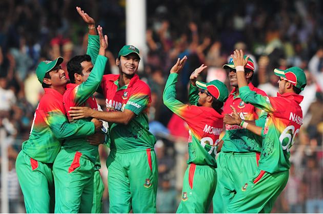 Bangladesh cricketer Abdur Razzak (2L) celebrates with his teammates after the dismissal of the unseen West Indies cricketer Devon Thomas during the second one day international cricket match between