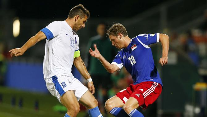 Liechtenstein's Hasler is challenged by Katsouranis of Greece during their World Cup qualifying soccer match in Vaduz