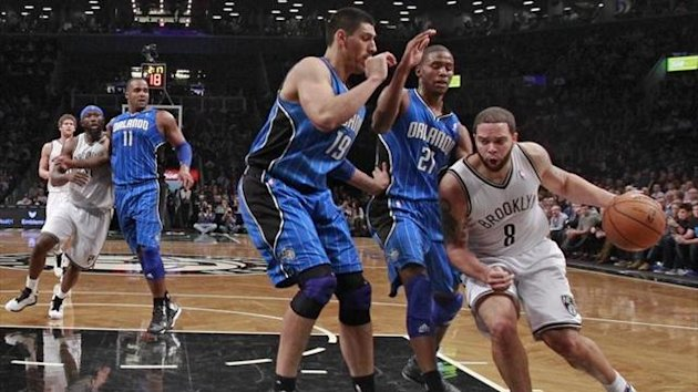 Brooklyn Nets guard Deron Williams (8) dribbles around Orlando Magic forwards Gustavo Ayon (19) and Moe Harkless (21) in the first quarter of their NBA basketball game in New York (Reuters)