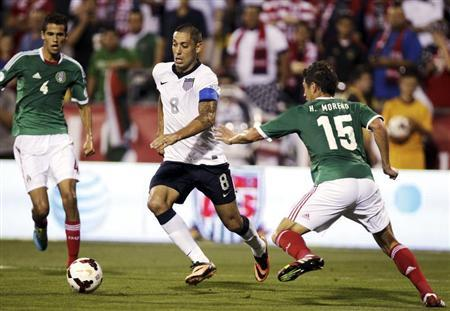 United States' Dempsey takes the ball past Mexico's Reyes and Moreno during the first half of their 2014 World Cup qualifying soccer match in Columbus