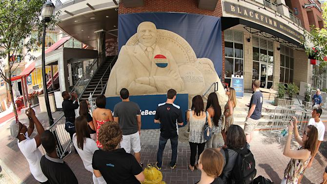 IMAGE DISTRIBUTED FOR VISITMYRTLEBEACH.COM - In this photograph taken by AP Images for VisitMyrtleBeach.com,  onlookers check out a 15.5 ton sand sculpture of President Barack Obama created by VisitMyrtleBeach.com Saturday, Sept. 1, 2012 in Charlotte, N.C. ahead of the Democratic National Convention. The sculpture, made from South Carolina sand, took five artists three days to complete. Myrtle Beach is located 175 miles from Charlotte and is widely considered to be the Carolina's favorite and most popular beach destination. (Jason E. Miczek/AP Images for VisitMyrtleBeach.com)