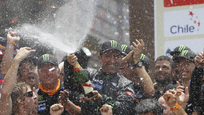 Mini driver Stephane Peterhansel, of France, center, sprays a bottle of sparkling wine over team members at the 2012 Argentina-Chile-Peru Dakar Rally podium ceremony in Lima, Peru, Sunday Jan. 15, 2012. The 46-year-old Peterhansel has won Dakar six times on motorbikes, and now four times in the car category. (AP Photo/Martin Mejia)