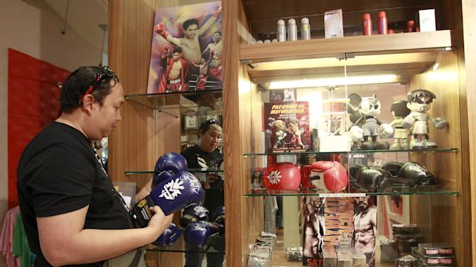 Fan looks at boxing gloves, signed by boxer Manny Pacquiao of the Philippines, on sale at 3,000 Philippine pesos ($68) per pair, at a store in Manila