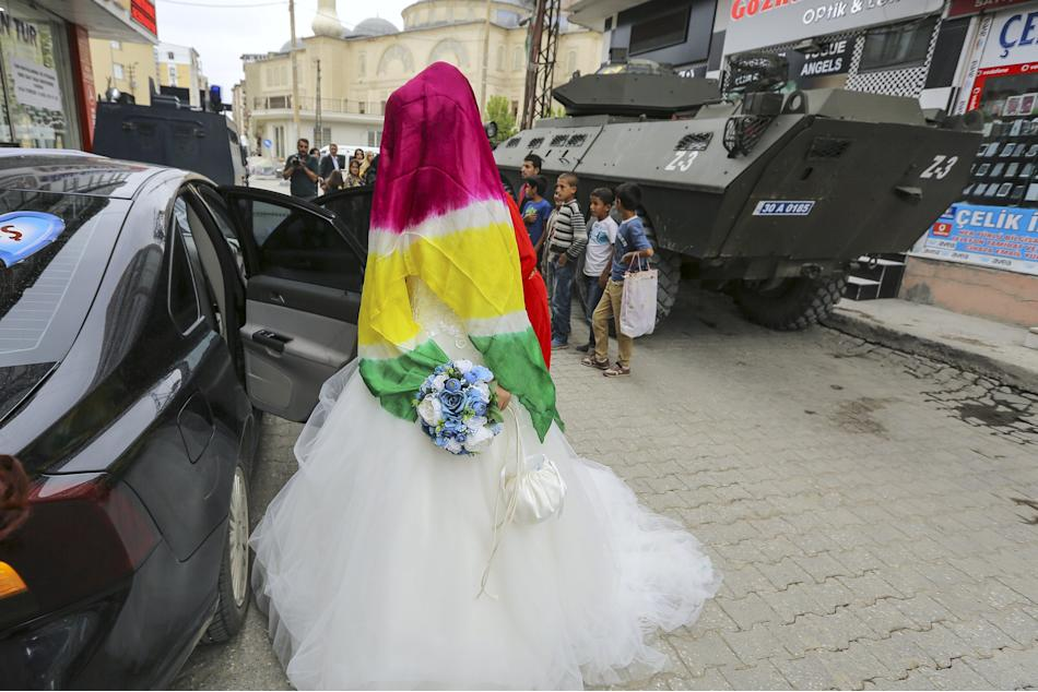 Bride Dilges Baskin, covered by scarf with yellow-red-green Kurdish colors, gets in wedding car, near armored police vehicles in Yuksekova in Kurdish-dominated southeastern Hakkari province of Turkey