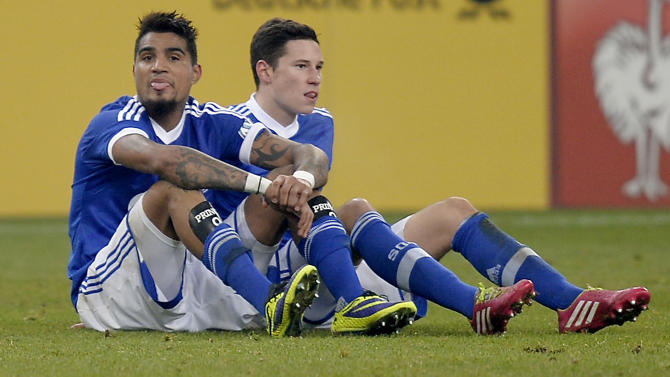 Schalke's Kevin-Prince Boateng, left, and Schalke's Julian Draxler, silt on the ground disappointed after losing during the German soccer cup third round match between FC Schalke 04 and TSG Hoffenheim in Gelsenkirchen, Germany, Tuesday, Dec. 3, 2013. Schalke was eliminated by Hoffenheim with 1-3