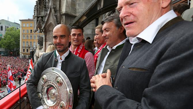 Josep Guardiola, head coach of Bayern Munich holds the German Championship  winners trophy as the team celebrate winning the German Championship title on the town hall balcony at Marienplatz in Munich