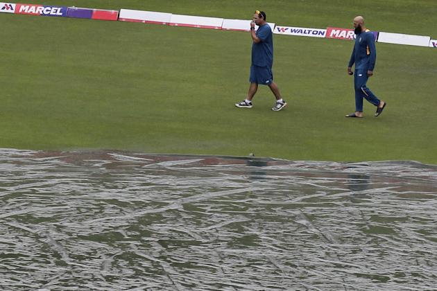 South Africa's captain Hashim Amla, right, inspects the field, as it rains on the fourth day of the second cricket test match between Bangladesh and South Africa in Dhaka, Bangladesh, Sunday, Aug.2, 2
