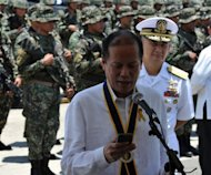 "Philippine President Benigno Aquino looks at his mobile phone after the navy's anniversary celebration at Fort San Felipe, on May 21, 2013. Aquino has announced a $1.8-billion military upgrade to help defend his country's maritime territory against ""bullies"", amid an ever-worsening dispute with China"