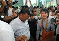 Myanmar opposition leader Aung San Suu Kyi (C) is surrounded by media representatives ahead of her departure at Yangon International Airport. She arrived in Switzerland on Wednesday on the first leg of a historic European tour