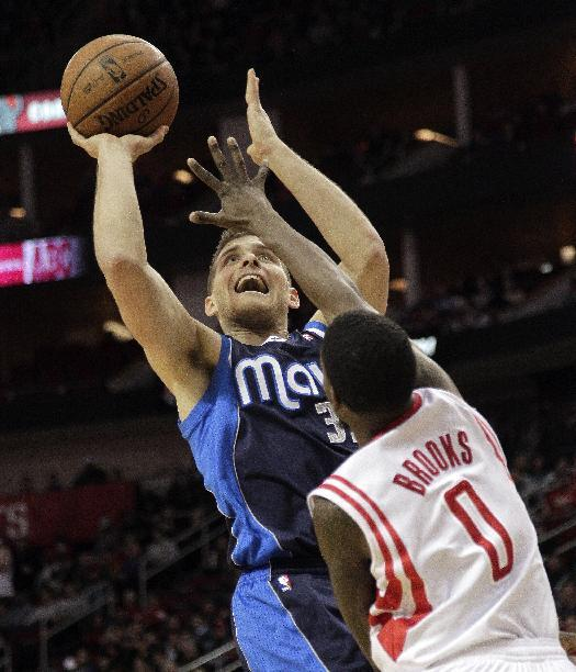 Dallas Mavericks guard Gal Mekel (33) shoots over Houston Rockets guard Aaron Brooks (0) during the first half of an NBA basketball game, Monday, Dec. 23, 2013, in Houston