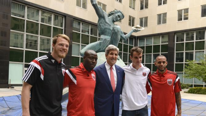 U.S. Secretary of State Kerry poses with players from Major League Soccer's DC United at the State Department in Washington