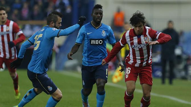Atletico's Oliver Torres, right, in action with Porto's Silvestre Varela, centre, and Porto's Steven Defour, left, during a Champions League Group G soccer match between Atletico Madrid and FC Porto, at the Vicente Calderon stadium in Madrid, Wednesday, Dec. 11, 2013