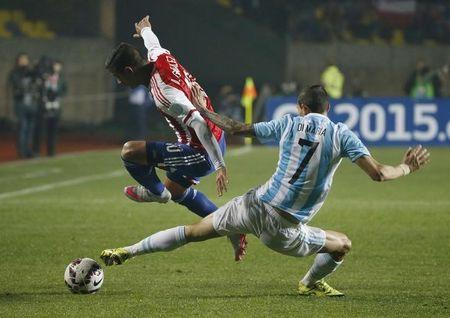 Paraguay's Gonzalez is challenged by Argentina's Di Maria during their Copa America 2015 semi-final soccer match at Estadio Municipal Alcaldesa Ester Roa Rebolledo in Concepcion