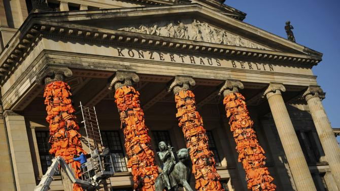 Workers bulid up an instalation by Chinese artist Ai Weiwei with life jackets left by migrants on Greek beaches on columns at the Schauspielhaus concert hall in Berlin