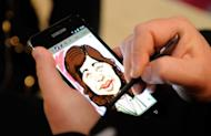 """An artist uses the Samsung's Galaxy Note at the International Consumer Electronics Show in Las Vegas in January. Using smartphones or tablets as digital """"wallets"""" will be common within a decade, largely replacing cash and credit cards, according to a Pew Research survey released on Tuesday"""
