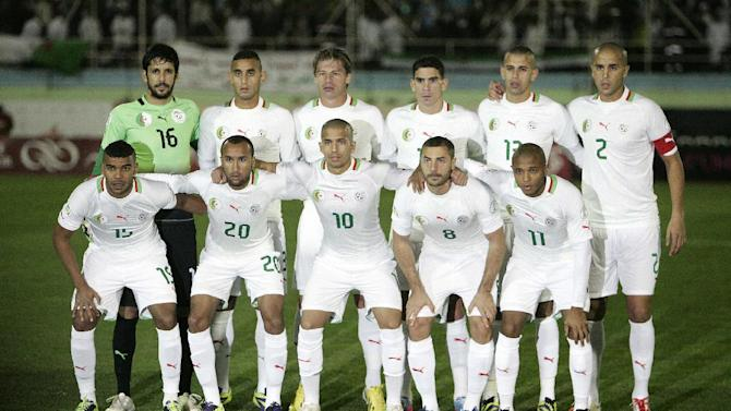 In this Nov. 19, 2013 file photo, Algeria's national soccer team poses prior to the start the World Cup qualifying soccer match between Burkina Faso and Algeria in Blida, Algeria. Background from left: Mohamed Lamine Zemmamouche, Faouzi Ghoulam, Mehdi Mostefa-sbaa, Carl Medjani, Islam Slimani and Madjid Bougherra. Foreground from left: El Arbi Hillel Soudani, Nacereddine Khoualed, Sofiane Feghouli, Medhi Lacen, Yacine Brahimi. The draw for the 2014 World Cup finals takes place Friday Dec. 6, 2013 near Salvador, Brazil. The 32 teams will be drawn into eight groups of four. The top two in each group will progress to the knockout stages. Twelve stadiums in twelve cities will host matches. ( AP Photo/ Anis Belghoul, File)
