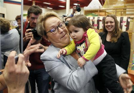 Parti Quebecois leader Pauline Marois holds a child at a children's indoor play centre in Blainville, Quebec March 25, 2014. REUTERS/Christinne Muschi