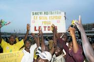 """Togolese supporters hold a placard reading """"Shevi Adebayor, Togo's only hope"""" as they celebrate at the end of the Africa Cup of Nations qualifier on October 14, 2012 in Lome. Togo beat Gabon 2-1 to qualify for the 2013 showpiece in South Africa"""