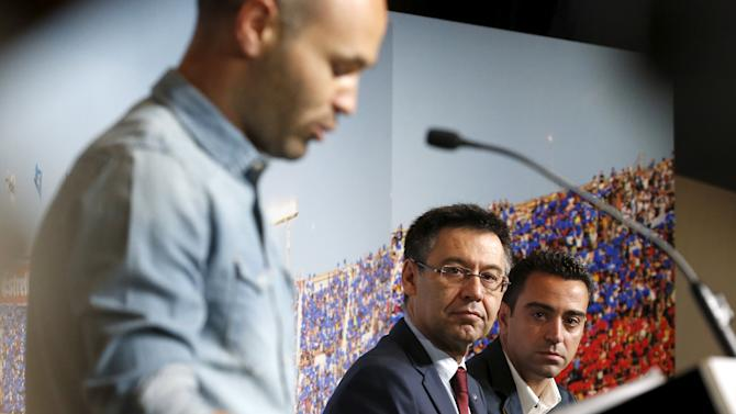 Barcelona's Xavi Hernandez listens to teammate Andres Iniesta speak near President Josep Maria Bartomeu during Xavi's farewell event at Auditori 1899 in Nou Camp stadium in Barcelona