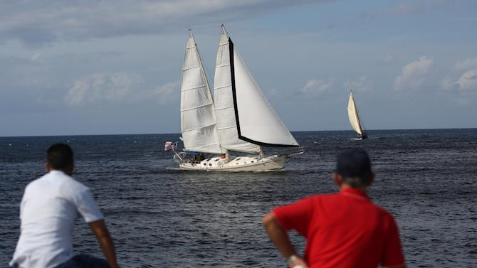 People look at the U.S. Irony sailing boat passing near by during a race between Havana and Cayo Hueso