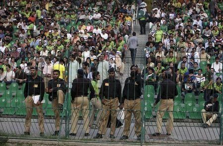 Pakistani policemen stand guard as spectators watch the first Twenty20 Cricket match between Pakistan and Zimbabwe in Lahore