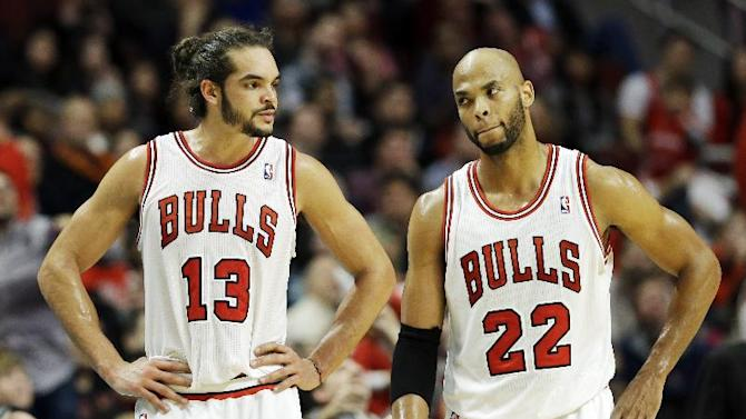 Chicago Bulls center Joakim Noah, left, and Taj Gibson stand on the court during the second half of an NBA basketball game against the Toronto Raptors in Chicago on Saturday, Dec. 14, 2013. The Raptors won 99-77