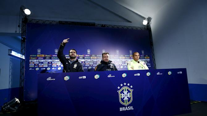 Brazil's head coach Dunga and Miranda listen to a question during a news conference before their team's training session at Santiago