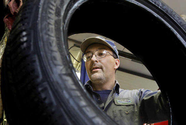 FILE - In this Dec. 11, 2014 file photo, John Phillips works at his auto repair shop in Decatur, Ill. Phillips is quick to say he's not a fan of President Barack Obama's health care law, but says he's