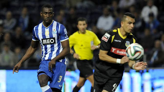 FC Porto's Jackson Martinez, left, from Colombia shoots to score his team's fourth goal past Arouca's Diego Queiroz, from Brazil, in a Portuguese League soccer match at the Dragao stadium, in Porto, Portugal, Sunday, March 9, 2014. Jackson Martinez scored once in Porto's 4-1 victory