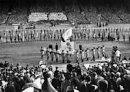 IOC President Sigfried Edström (centre) holds the Olympic flag during the closing ceremony of the 1948 Olympic Games at Wembley Stadium in London. London is the first city to host a third Olympic Games, but the modest Games of the last century were worlds away from today's glossy extravaganzas