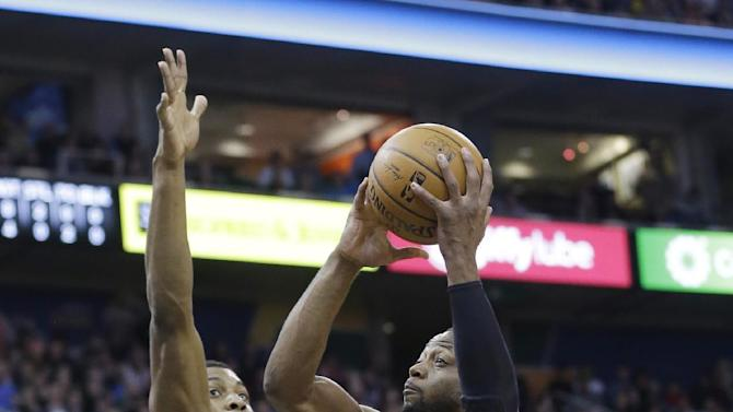 Miami Heat's Dwyane Wade (3) goes to the basket as Utah Jazz's Derrick Favors, left, defends during the first quarter of an NBA basketball game Saturday, Feb. 8, 2014, in Salt Lake City. (AP Photo/Rick Bowmer)