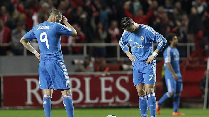 Real Madrid's Cristiano Ronaldo from Portugal, right, and Karim Benzema from France, left, react during their La Liga soccer match against Sevilla at the Ramon Sanchez Pizjuan stadium, in Seville, Spain on Wednesday, March 26, 2014
