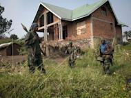 Rebels of the M23 group stand near a deserted house after their troops entered the town of Rutshuru near the Ugandan border on July 8, 2012. UN and Democratic Republic of Congo troops are reinforcing the key city of Goma in the east of the country to guard against attack by rebels who have seized ground in recent days, UN officials said