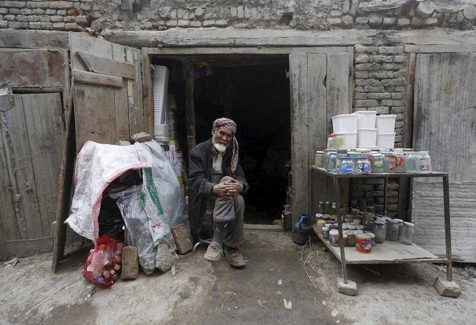 An Afghan man selling empty cans waits for customer at his shop in Kabul