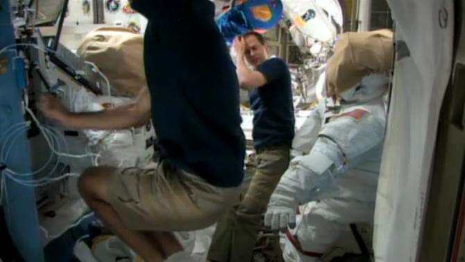 In this image made from video provided by NASA, astronauts Chris Cassidy, foreground, and Tom Marshburn prepare for a possible spacewalk from the International Space Station on Friday, May 10, 2013. NASA will decide later Friday if the two astronauts will step outside the station to work on a leaking coolant line. The line chills power systems but power was rerouted and is operating normally. The six-member crew is not in danger. (AP Photo/NASA)