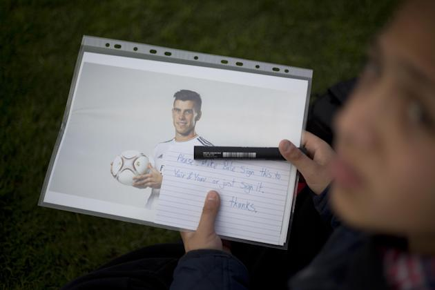 Mahmud Bazbaz holds a photograph of Wales international and Real Madrid soccer player Gareth Bale to ask for an autograph as he wait for him to arrive at an event with Jewish and Arab children from co