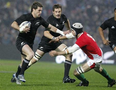 Jones moves in to tackle Jane as McCaw backs up during their Rugby Union test match in Hamilton