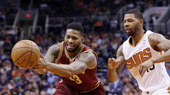 Cleveland Cavaliers' Alonzo Gee, left, loses the ball as it is tipped away by Phoenix Suns' Marcus Morris, right, during the first half of an NBA basketball game on Wednesday, March 12, 2014, in Phoenix