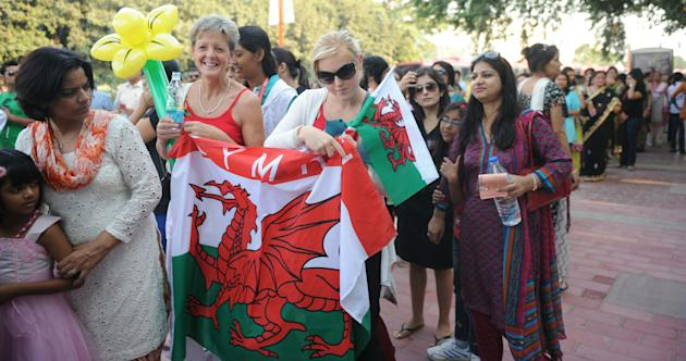 Laura Edwards (3 R) and Sue Davies (2 R), girlfriend and mother of badminton player James Philips of Wales, hold the Welsh flag as they queue to enter Jawaharlal Nehru Stadium to attend the Commonwealth Games opening ceremony in New Delhi on October 3, 2010. The Games are due to open on the evening of October 3 with a glittering opening ceremony that organisers hope will erase memories of a shambolic run-up to the event. The Games, in which about 5,000 athletes will compete over 11 days of sport, have teetered on the brink of collapse in recent weeks over shabby accommodation, untested venues and a host of other health and security fears. AFP PHOTO / RAVEENDRAN (Photo credit should read RAVEENDRAN/AFP/Getty Images)