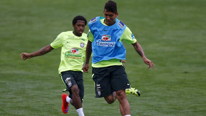 Brazilian national soccer team players Firmino and Fred fight for the ball during a training session in Teresopolis