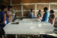 Residents look at the coffins of those killed in the landslides that buried mining tunnels and tents in the gold-rich town of Pantukan, Compostela Valley, in the Philippines. Philippine officials say there is little chance of finding more survivors, with 22 people likely killed in the disaster