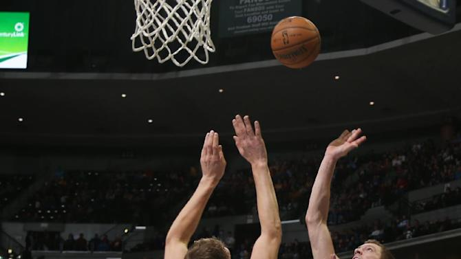 Golden State Warriors forward David Lee, right, lobs a shot for a basket over Denver Nuggets center Timofey Mozgov, of Russia, in the first quarter of an NBA basketball game in Denver, Monday, Dec. 23, 2013
