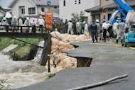 Japanese soldiers and other workers repair a collapsed bank of the Koura River in Kurume, Fukuoka Prefecture, on July 14. Flood victims in Japan have begun a full-scale clean-up operation after record rainfall forced hundreds of thousands to flee and left at least 32 dead or missing