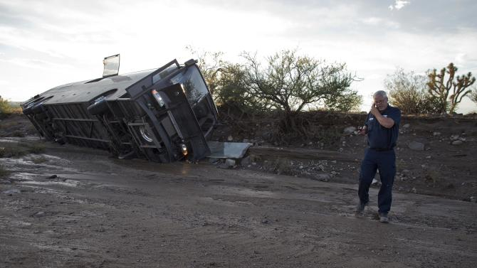 A tow truck driver talks on his cell phone after assessing the location of a tour bus which was caught in flash flood waters and pushed down a wash about 300 yards from the road, Sunday, July 28, 2013, near Dolan Springs, Ariz. None of the 33 passengers or driver returning to Las Vegas from a trip to the west rim of the Grand Canyon were hurt in the crash which happened as Northern Arizona was hit with a second day of heavy rain. (AP Photo/Julie Jacobson)