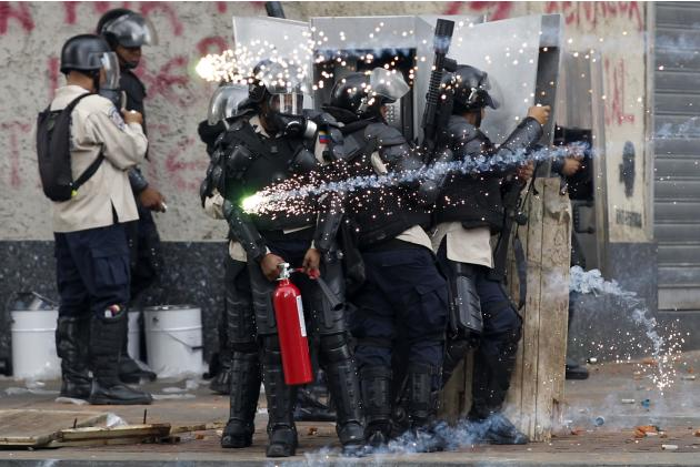 Police take cover from fire crackers thrown by anti-government protesters during riots with police in Caracas