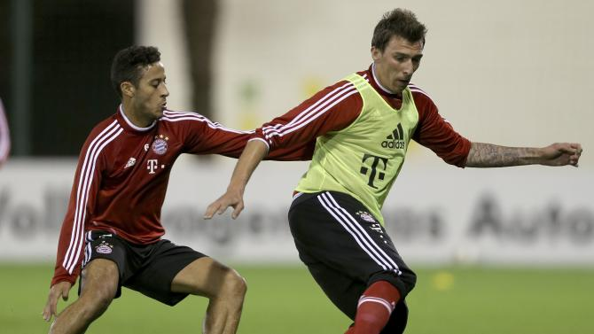 Bayern Munich's Mario Mandzukic fights for the ball with Thiago Alcantara during a training session at Aspire Academy for Sports Excellence in Doha