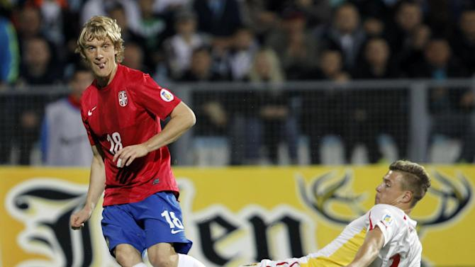Serbia's Dusa Basta, left, challenges for the ball with Macedonia's Ezdjan Alioski during their World Cup 2014 Group A qualifying soccer match at the City Stadium in Jagodina, Serbia, Tuesday, Oct. 15, 2013