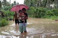 A woman carrying her child wades through a flooded road brought about by heavy rains due to Typhoon Bopha, as she evacuates to a safer place, in Pantukan town on the southern island of Mindanao on December 4, 2012. Parts of Mindanao remained without power and communications, with food and clean water in limited supply after Bopha carved a path of destruction.
