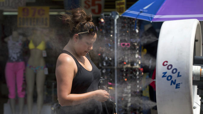 A tourist stops to cool off in a misting fan while walking along The Strip, Friday, June 28, 2013 in Las Vegas. A blazing heat wave expected to send the mercury soaring to nearly 120 degrees in Phoenix and Las Vegas settled over the West on Friday, threatening to ground airliners and raising fears that people and pets will get burned on the scalding pavement. (AP Photo/Julie Jacobson)